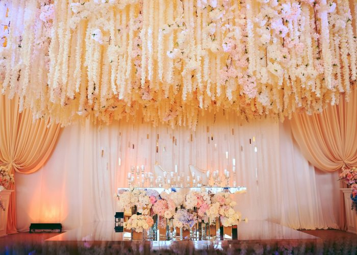 groom and bride's wedding table decorated with tender flowers and whitecandles